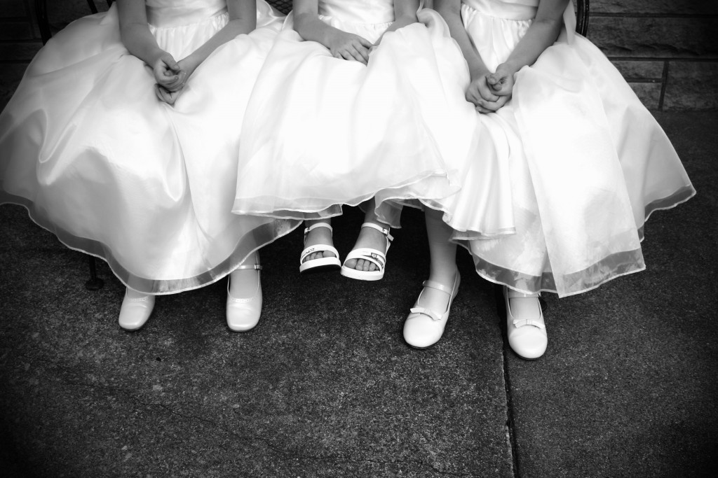 Three little flower girls were sitting outside on a bench. This is a picture of their hands on their dresses with their feet dangling.