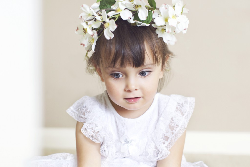 Little Girl With a White Dress and Flower Wreath on Head.