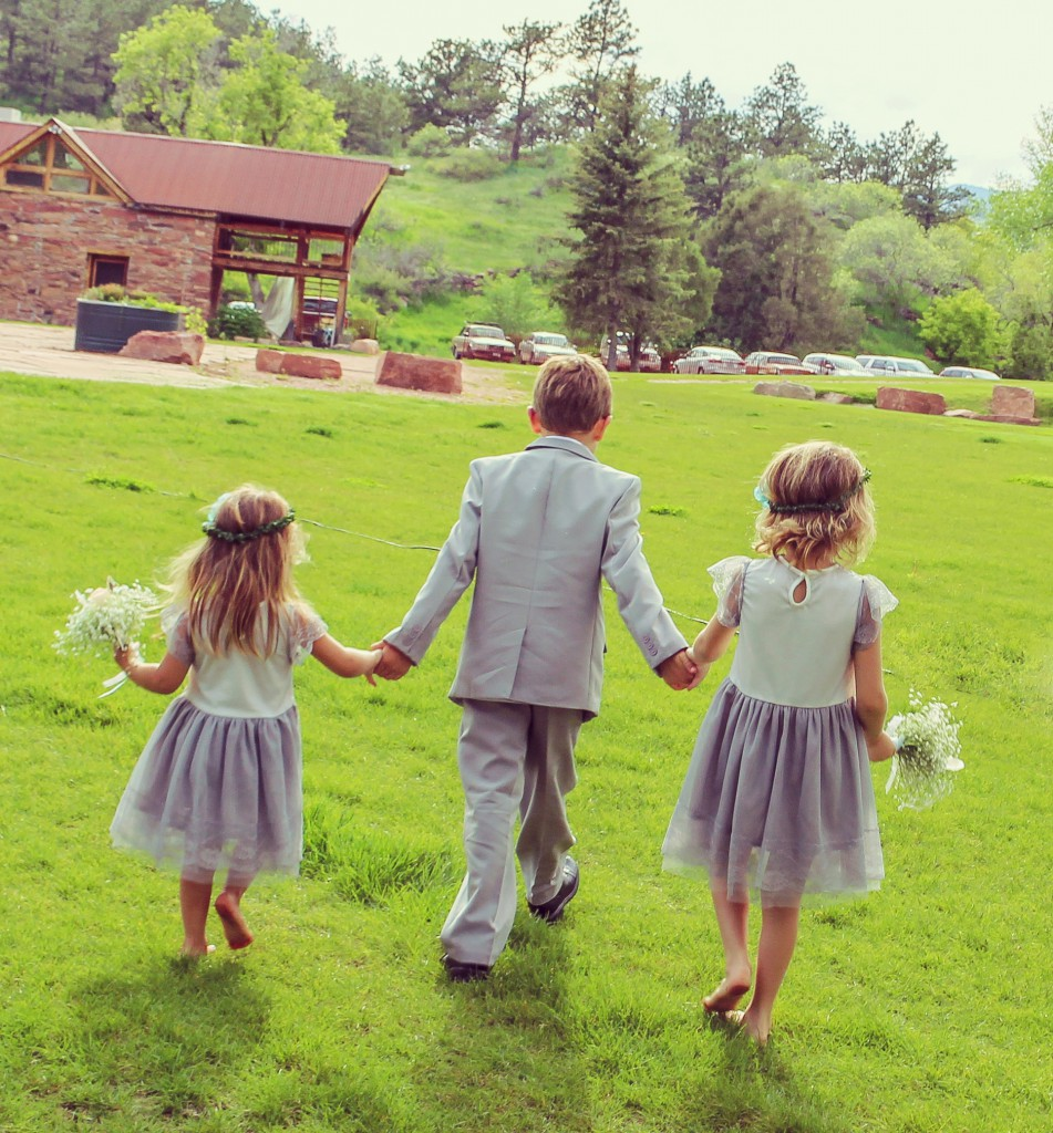 From behind, a boy holds hands with two little girls, wedding party