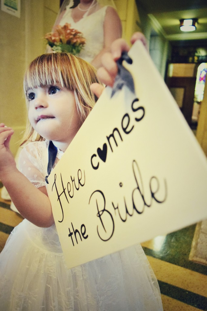 Little girl holds up a sign announcing the bride is coming down the aisle