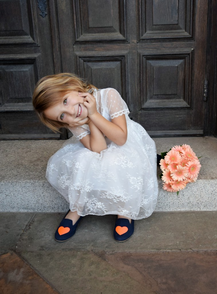 An asorable little girl sits on the church steps with her head I hands