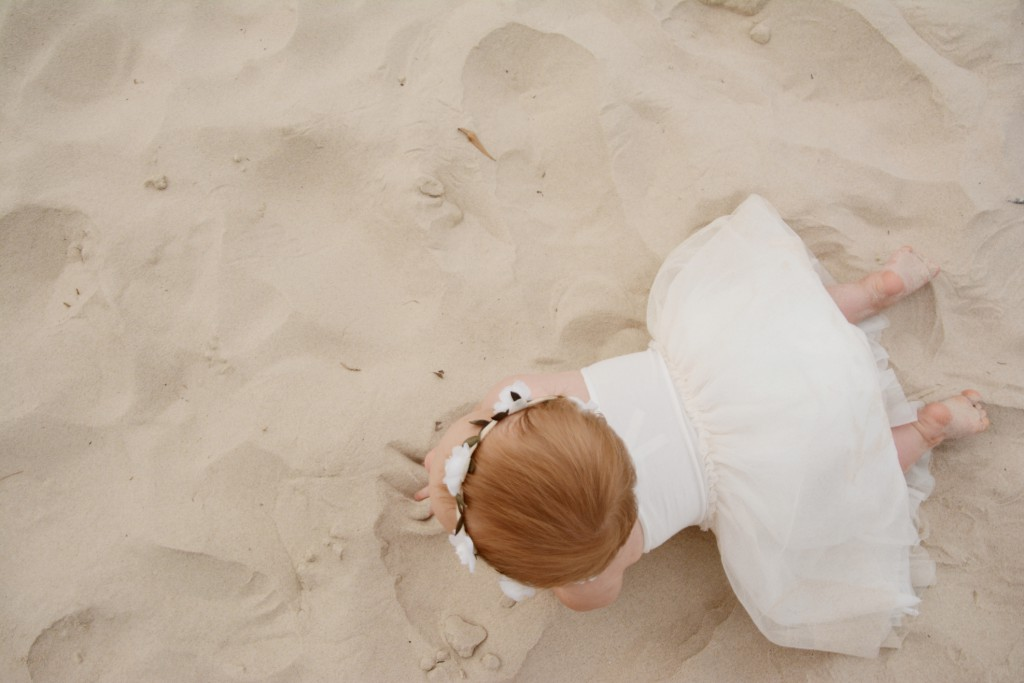 A cute baby wearing a dress crawling on the sand.